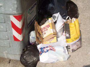 Cassonetto con immondizia indifferenziata (compresa la carta) lasciata per terra